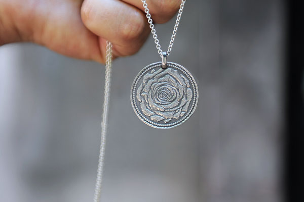 Männerhand mit Silberkette mit Rosenbund-Taler